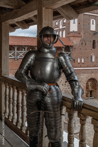 Photo  Knight in full armor with a sword against the background of the ancient walls of