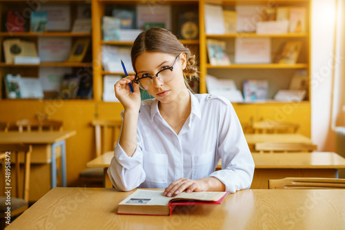 girl with glasses sitting at a table with a book in the classroom, holding a pen Canvas Print
