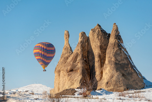 Photo  colorful balloon over the extraordinary rocks formations rock hills on snowy win