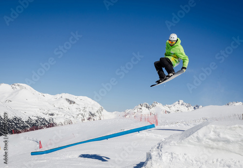 Poster Glisse hiver Jumping snowboarder with a blue and sunny sky in Zermatt, the swiss Alps