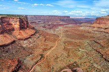 Trail Through The Deep Desert Gorge Of Canyonlands National Park In Utah