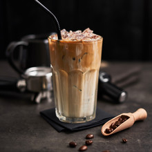 Ice Coffee With Cream In A Tall Glass And Coffee Beans, Portafilter, Tamper And Milk Jug On Dark Concrete Table Over Black Wooden Background. Cold Summer Drink. Copy Space For Text. Square Crop.