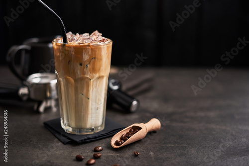 Fotografie, Obraz Ice coffee with cream in a tall glass and coffee beans, portafilter, tamper and milk jug on dark concrete table over black wooden background