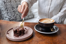 A Woman Cutting Brownie Cake With Fork With Coffee Cup On Wooden Table In Cafe