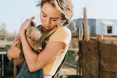 Young volunteer with a piglet, The Sanctuary at Soledad, Mojave Canvas Print