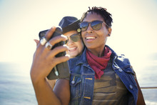 Two Smiling Women Taking A Selfie Near The Beach