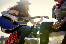 Woman Playing A Guitar With A Friend Outdoors