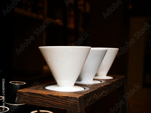 Fotografie, Obraz  Three traditional ceramic coffee filters on wooden desk in a coffee shop
