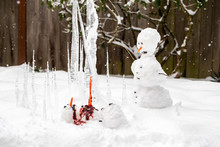 Bloody Dead Snowman Impaled On A Sharp Icicle During A Winter Storm