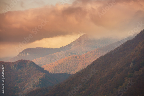 Foto auf Gartenposter Gebirge Beautiful autumn scenery in the mountains with mist clouds, pine trees and colorful foliage