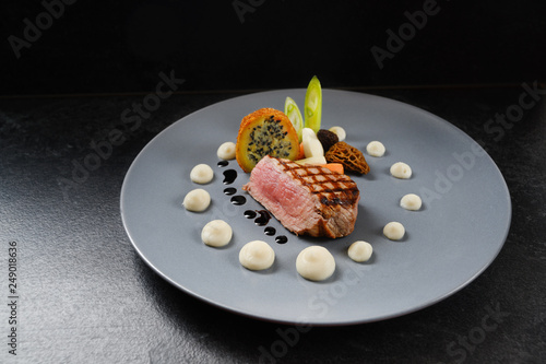 Fototapeta menu main course with roasted veal, morels and vegetables on a blue gray plate on a dark table, copy space obraz