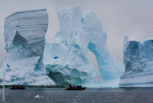 People on boats sailing along icebergs.