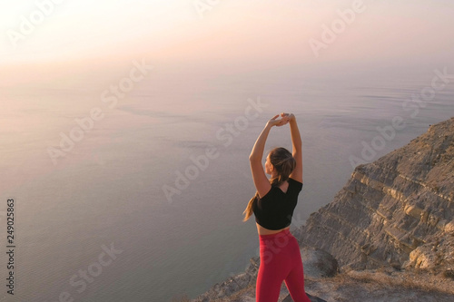 Fotografija  Beautiful view of woman doing yoga stretching on the mountain with sea view at sunset