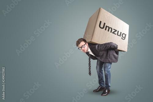 Fototapeta Mann trägt einen großen Karton mit der Aufschrift Umzug