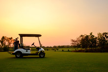 Golf Cart Car In Fairway Of Golf Course With Fresh Green Grass Field And Cloud Sky And Tree  On Sunset Time