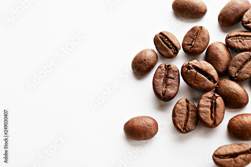 Foto op Canvas koffiebar Roasted brown coffee beans scattered on white table with a lot copy space for text. Flat lay composition. Close up, top view, background.