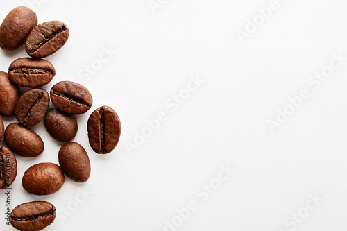 Fototapeta  Roasted brown coffee beans scattered on white table with a lot copy space for text