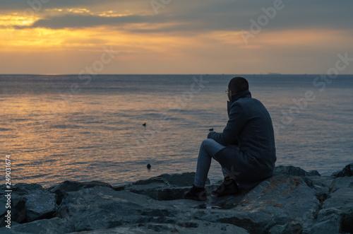 Fotografie, Obraz  Man is  sitting on a ledge of a sea,