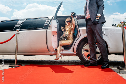 Fotomural  Driver helping VIP woman or star out of limo on red carpet