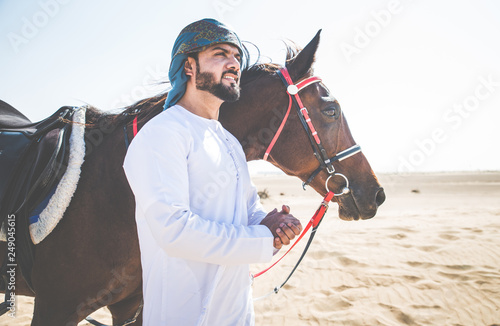 Spoed Foto op Canvas Abu Dhabi Young adult with Kandura, the emirates traditional clothes, riding his horse in the desert