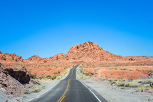 Two Lane Road Through The Desert Running Toward The Mountain On The Horizon