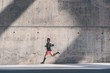 Leinwanddruck Bild - Muscular Male athlete sprinter running fast,exercising outdoors,jogging outside against gray concret background with copy space area for text message or ad content.Side view,full length