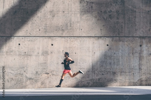 Fototapeta  Muscular Male athlete sprinter running fast,exercising outdoors,jogging outside against gray concret background with copy space area for text message or ad content