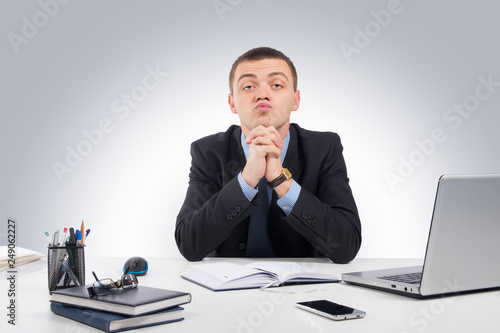 Fényképezés  Serious businessman skeptically looking at you sitting at his desk