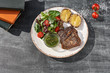 Middle grilled beef steak, with potatoes with cheese and fresh salad, on a wooden table, close-up.