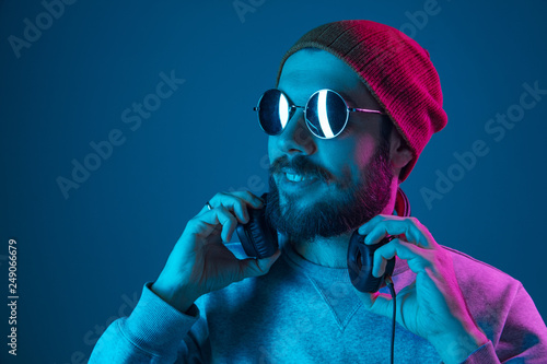 Papiers peints Magasin de musique Enjoying his favorite music. Happy young stylish man in hat and sunglasses with headphones listening and smiling while standing against blue neon background