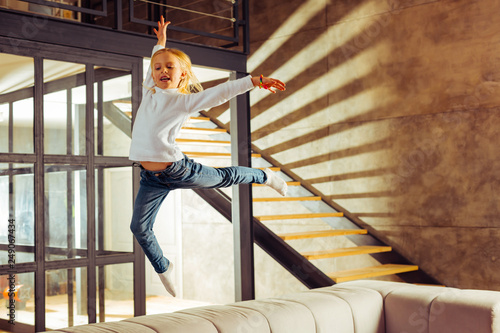 Positive delighted little female jumping on sofa Wallpaper Mural