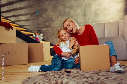 Fotografering Positive delighted female person caressing her daughter