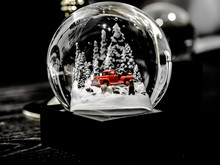 Snow Globe Merry Christmas New Year Winter With Snow Falling And Christmas Trees Present On The Table, Modern Concept For Christmas.