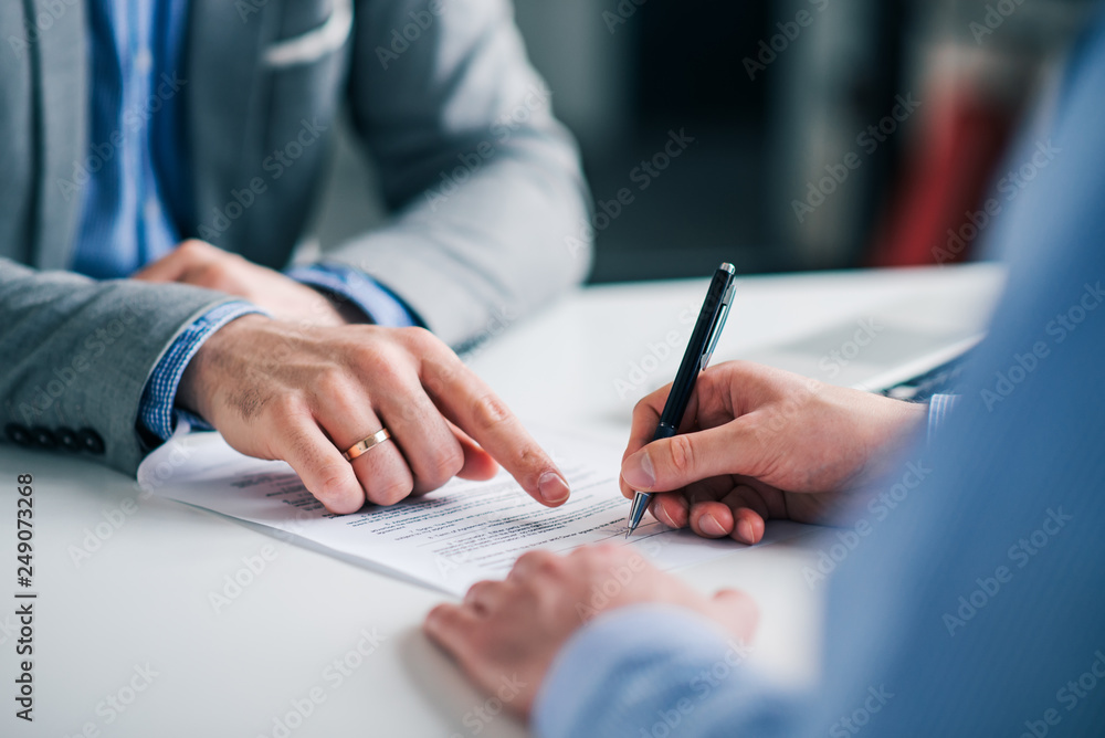 Fototapeta Businessmen hand's pointing where to sign a contract, legal papers or application form.