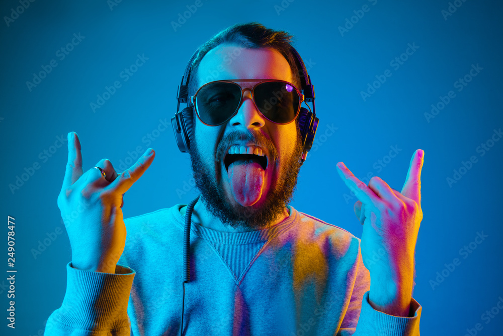 Fototapety, obrazy: Enjoying his favorite music. Happy young stylish man in sunglasses with headphones listening sound and smiling while standing against blue neon background