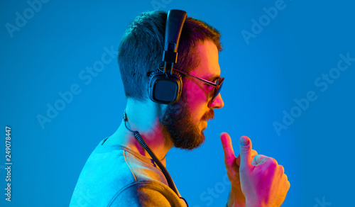 Enjoying his favorite music. Serious young stylish man in sunglasses with headphones listening sound while standing against blue neon background - 249078447