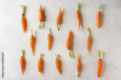 Young mini carrot in row over white marble background Fototapete
