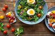 Fresh vegetable salad with eggs and mix of cherry tomatoes on wooden table.