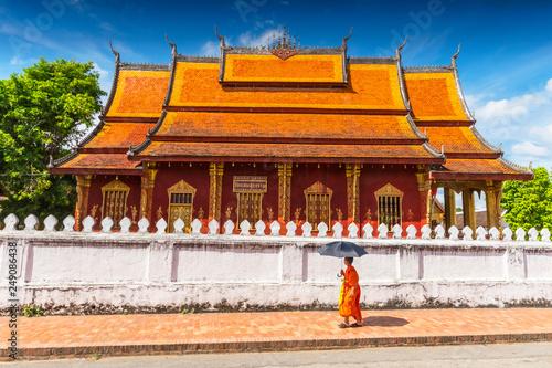 Fotografia  A Buddhist monk walks by the Wat Sen Temple in Luang Prabang, Laos