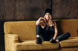 Portrait of a beautiful fashionable woman, blonde, jeans, hat, on a yellow sofa