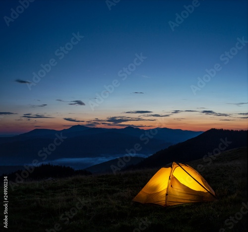 Orange lighted tent in mountains under evening sky