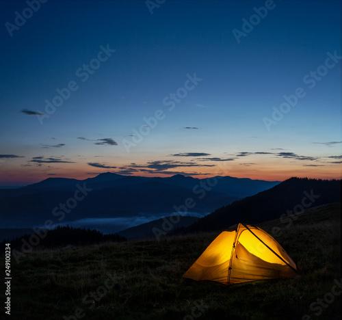Door stickers Black Orange lighted tent in mountains under evening sky