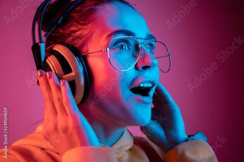 Foto op Plexiglas Beauty Surprised pretty woman with headphones listening to music over red neon background at studio.