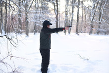 A Man With A Gun In His Hands Is Aiming In The Winter Forest.