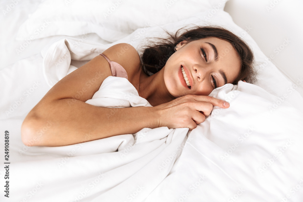 Fototapeta Photo of relaxed woman 20s with dark hair smiling, while lying in bed on white pillow after sleep or nap