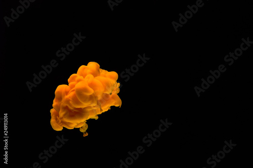Fotografia  Yellow acrylic paint in water isolated on black