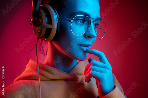 Fashion pretty woman with headphones listening to music over red neon background at studio. - 249116684