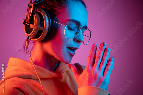 Fotografie, Obraz  Fashion pretty woman with headphones listening to music over red neon background at studio