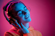 canvas print picture - Fashion pretty woman with headphones listening to music over red neon background at studio.
