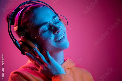 Photographie Fashion pretty woman with headphones listening to music over red neon background at studio